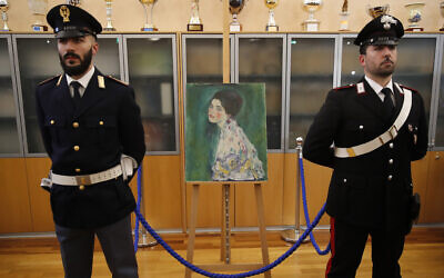 An Italian Policeman, left, and a Carabiniere, paramilitary police officer, stand beside a painting which was found last December near an art gallery and believed to be the missing Gustav Klimt's painting 'Portrait of a Lady' during a press conference in Piacenza, Italy, Jan. 17, 2020 (AP Photo/Antonio Calanni)