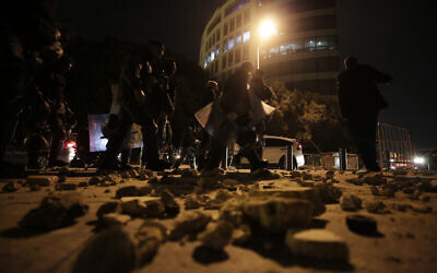 Lebanese police walk after dispersing a protest in Beirut, Lebanon, January 18, 2020. (AP/Hassan Ammar)