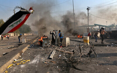 Anti-government protesters close a street while security forces use tear gas during clashes in central Baghdad, Iraq, Jan. 20, 2020 (AP Photo/Khalid Mohammed)