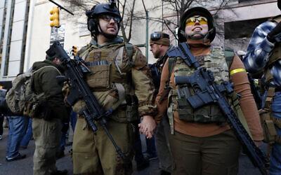 Demonstrators stand outside a security zone before a pro-gun rally, Monday, Jan. 20, 2020, in Richmond, Va. (AP Photo/Julio Cortez)