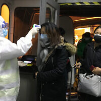 Health Officials in hazmat suits check body temperatures of passengers arriving from the city of Wuhan, Jan. 22, 2020, at the airport in Beijing, China (AP Photo Emily Wang)