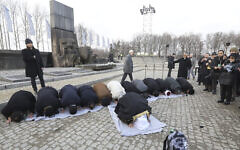 """A delegation of Muslim religious leaders perform prayers during a visit to the former Nazi death camp of Auschwitz,  in what organizers called """"the most senior Islamic leadership delegation"""" to visit, in Oswiecim, Poland, January 23, 2020. (American Jewish Committee via AP)"""