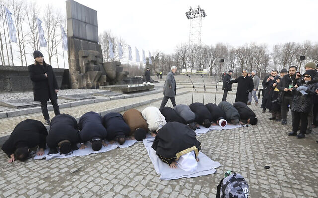 """A delegation of Muslim religious leaders perform prayers during a visit to the former Nazi death camp of Auschwitz,  in what organizers called 鈥渢he most senior Islamic leadership delegation"""" to visit, in Oswiecim, Poland, January 23, 2020. (American Jewish Committee via AP)"""