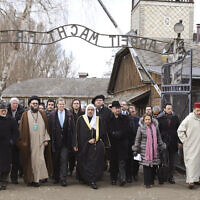 """A delegation of Muslim religious leaders at the gate leading to the former Nazi German death camp of Auschwitz, together with a Jewish group in what organizers called 鈥渢he most senior Islamic leadership delegation"""" to visit the former Nazi death camp, in Oswiecim, Poland, January 23, 2020. (American Jewish Committee via AP)"""