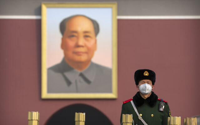 A paramilitary policeman wears a face mask as he stands guard near the large portrait of Chinese leader Mao Zedong at Tiananmen Gate adjacent to Tiananmen Square in Beijing on January 27, 2020. (AP Photo/Mark Schiefelbein)