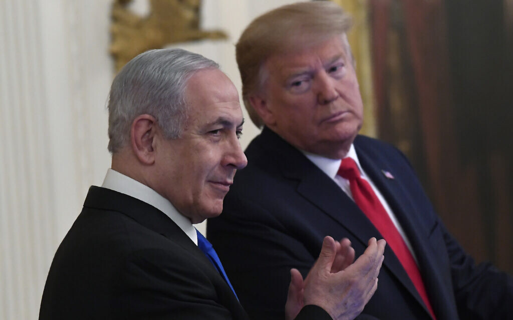 """US President Donald Trump, right, looks over to Prime Minister Benjamin Netanyahu, left, during an event in the East Room of the White House in Washington, January 28, 2020, at which Trump unveiled his """"Peace to Prosperity"""" vision for an Israeli-Palestinian accord. (AP/Susan Walsh)"""