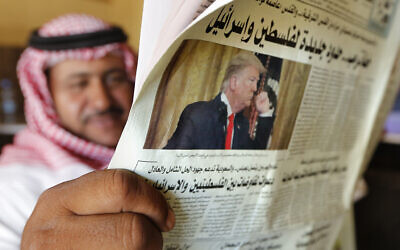 A man holds the daily Asharq Al-Awsat newspaper fronted by a picture of President Donald Trump, at a coffee shop in Jiddah, Saudi Arabia on January 29, 2020. (AP Photo/Amr Nabil)