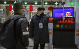 A security officer directs a man past a thermal imaging camera at a subway station in Beijing, January 29, 2020. (AP Photo/Mark Schiefelbein)