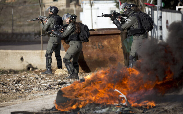 Israeli troops take their position during clashes with Palestinian demonstrators as they protest Middle East peace plan announced Tuesday by US President Donald Trump at Beit El checkpoint, near the West Bank city of Ramallah, Wednesday, Jan 29, 2020 (AP/Majdi Mohammed)
