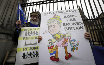 Anti-Brexit campaigners hold banners outside Parliament in London on January 30, 2020. (AP Photo/Kirsty Wigglesworth)