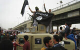 Islamic State group militants wave al-Qaida flags as they patrol in a commandeered Iraqi military vehicle in Fallujah, Iraq on March 30, 2014. (AP Photo, File)
