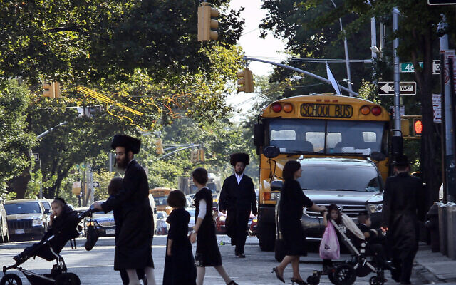 Illustrative: In this September 20, 2013 file photo, children and adults cross a street in front of a school bus in Borough Park, a neighborhood in the Brooklyn borough of New York that is home to many ultra-Orthodox Jewish families. (AP/Bebeto Matthews, File)