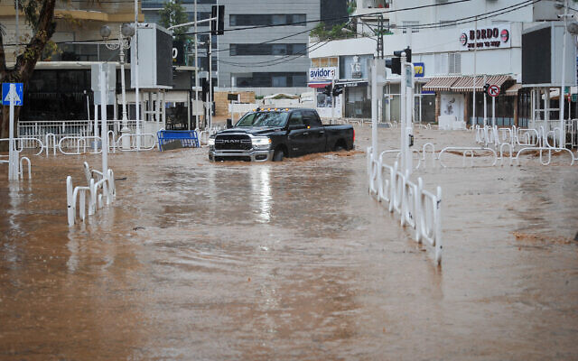 A car drives along a flooded road in the northern Israeli city of Nahariya on January 8, 2020, after a river burst it banks. Some 40%, or 250 millimeters (9.8 inches), of the city's average annual rainfall fell from January 3 to 9, that year. (Meir Vaknin/Flash90)