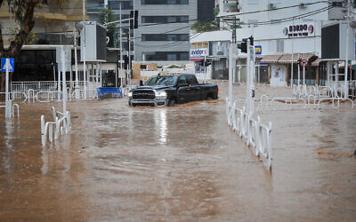 A car drives on a flooded road in the northern city of Nahariya on January 8, 2020. (Meir Vaknin/Flash90)