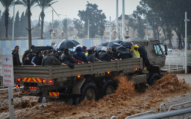 A military truck evacuates residents through a flooded road in the northern city of Nahariya, on a stormy winter day, on January 8, 2020. (Meir Vaknin/Flash90)