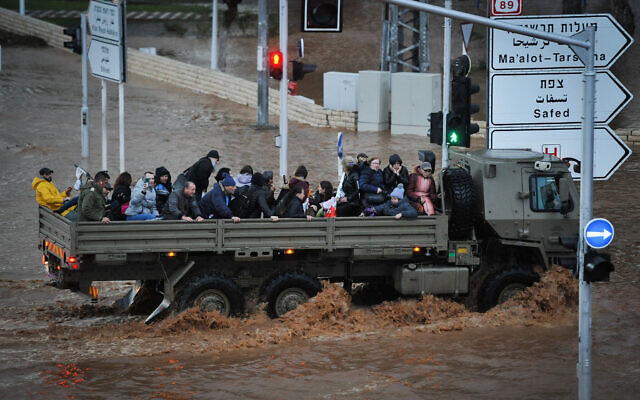 A military vehicle carries people across a flooded road in the northern city of Nahariya on January 8, 2020. (Meir Vaknin/Flash90)
