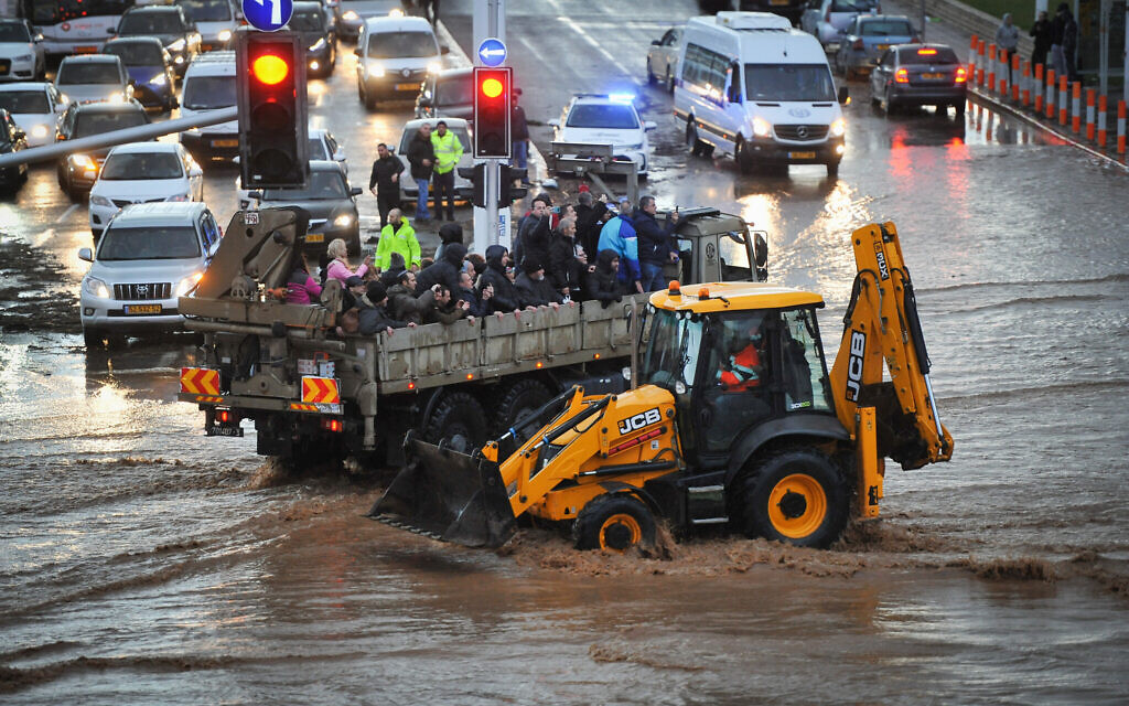 A military truck evacuates Israeli citizens through a flooded road in the northern Israeli city of Nahariya, on a stormy winter day, on January 8, 2020. (Meir Vaknin/Flash90)