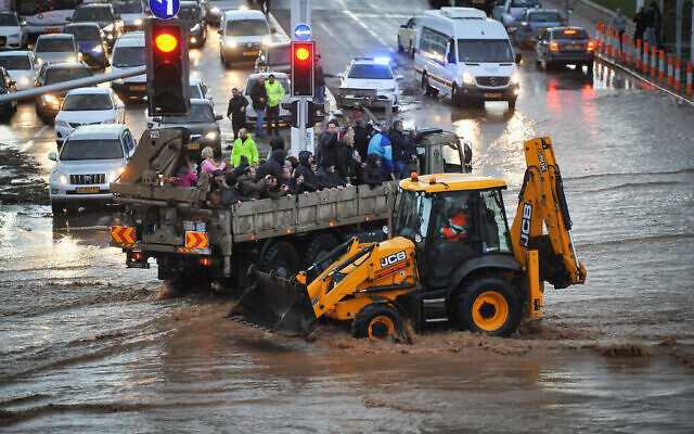 A military truck evacuates Israeli citizens through a flooded road in the northern city of Nahariya on a stormy winter day, January 8, 2020. (Meir Vaknin/Flash90)
