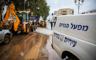 Nahariya municipality workers work in the streets of the northern Israeli city which was suffered severe flooding due to heavy rain storms, January 9, 2020. (David Cohen/Flash90)