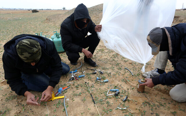 Young Palestinian men prepare flammable objects to be launched toward Israel, near Rafah in the southern Gaza Strip, January 18, 2020. (Abed Rahim Khatib/Flash90)