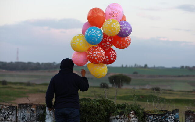 A bunch of balloons attached to an incendiary device is prepared to be flown into Israel, near the Israel-Gaza border east of Al-Bureij refugee camp in the central Gaza Strip, January 22, 2020. (Ail Ahmed/ Flash90)