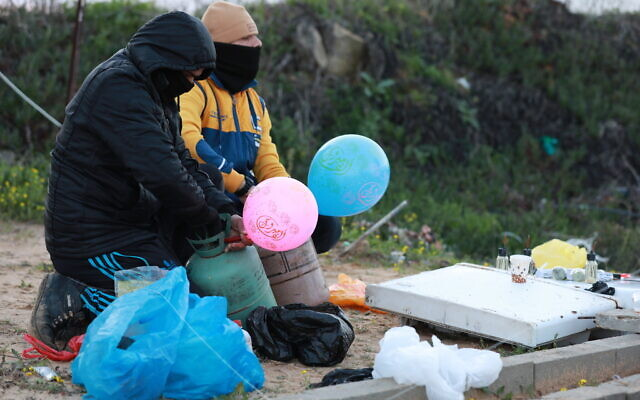 Masked Palestinians prepare an incendiary device with what appears to be gas canisters and balloons to be flown into Israel, near the Israel-Gaza border east of Al-Bureij refugee camp in the central Gaza Strip, January 22, 2020. (Ail Ahmed/Flash90)
