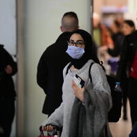 A woman wears a face mask in the arrivals hall of Ben Gurion Airport on January 28, 2020. (Tomer Neuberg/Flash90)