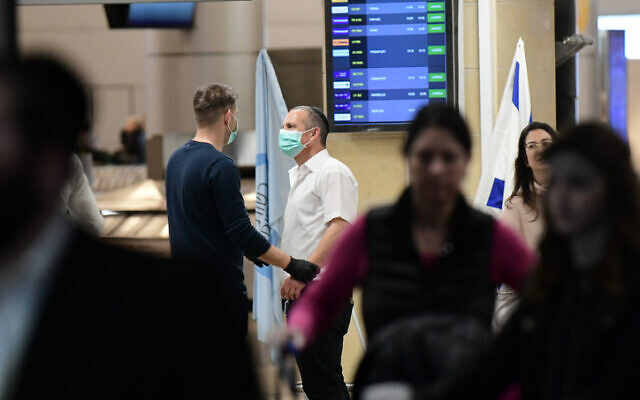 People wearing face masks at the arrival hall of the Ben Gurion Airport, near Tel Aviv, January 28, 2020. (Tomer Neuberg/Flash90)