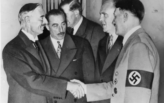 British prime minister Neville Chamberlain, left, shakes hands with Hitler to seal the Munich Agreement. (Public domain)