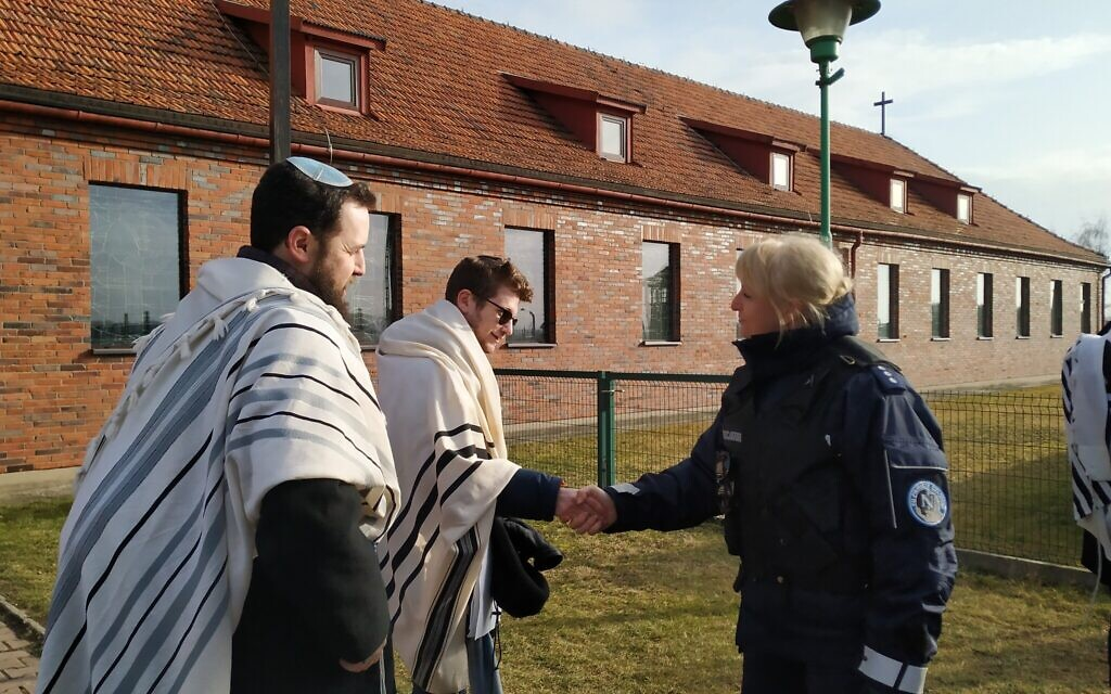 Rabbi Shabbos Kestenbaum shakes hands with a police officer after he and three others protested the location of a church in a former SS headquarters across from the former Nazi death camp Birkenau, January 27, 2020. (Yaakov Schwartz/ Times of Israel)