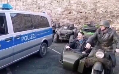 Screen capture from video of a man dressed as Hitler riding in a motorcycle sidecar at an event in in Augustusburg, near Chemnitz, Germany, January 2020. (Twitter)