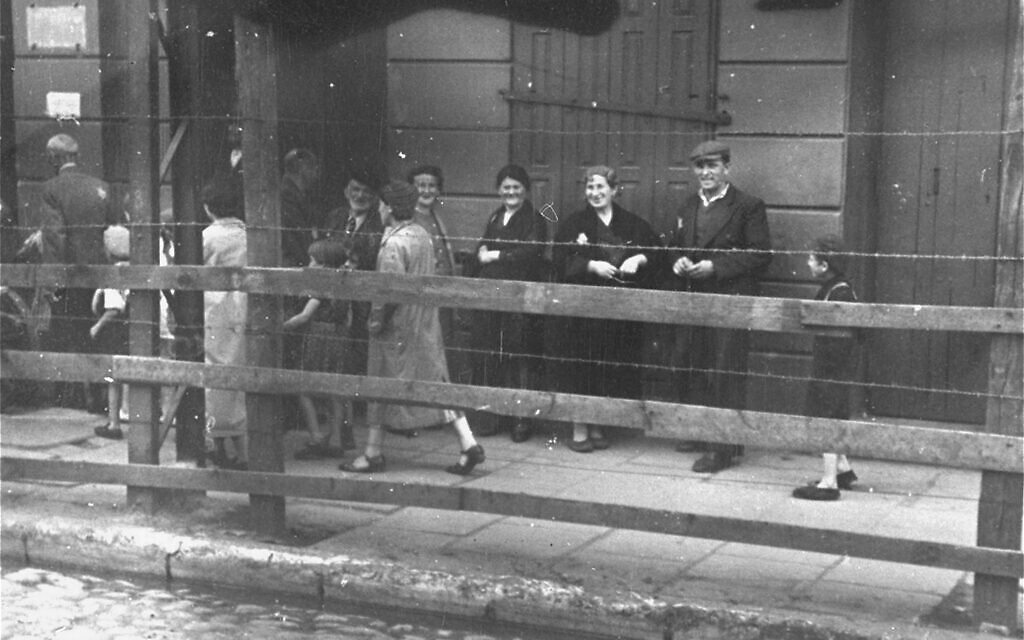Lodz Ghetto Jews behind the wooden and barbed wire fence that separated the ghetto from the rest of the city, 1940-1941. (Courtesy of Daniel B. Schwartz)