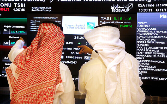 Saudi stock market officials watch the market screen displaying Saudi Arabia's state-owned oil company Aramco after its initial public offering (IPO) on the Riyadh's stock market in Riyadh, Saudi Arabia, Dec. 11, 2019. (AP Photo/Amr Nabil)