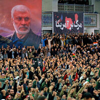 Worshipers in Iran chant slogans during Friday prayers ceremony by a banner showing slain Iranian Revolutionary Guard general Qassem Soleimani, left, and Iraqi Shiite senior militia commander Abu Mahdi al-Muhandis, who were killed in Iraq in a US drone attack on January 3, and a banner which reads in Persian: 'Death To America,' at Imam Khomeini Grand Mosque in Tehran, Iran, January 17, 2020. (Office of the Iranian Supreme Leader via AP)