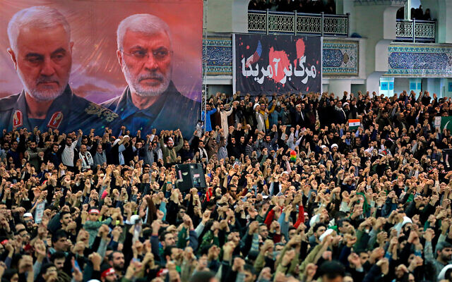 Worshipers in Iran chant slogans during Friday prayers ceremony by a banner showing slain Iranian Revolutionary Guard Gen. Qassem Soleimani, left, and Iraqi Shiite senior militia commander Abu Mahdi al-Muhandis, who were killed in Iraq in a US drone attack on January 3, and a banner which reads in Persian: 'Death To America,' at Imam Khomeini Grand Mosque in Tehran, Iran, January 17, 2020. (Office of the Iranian Supreme Leader via AP)