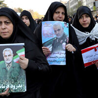 Mourners holding posters of Iranian general Qassem Soleimani attend a funeral ceremony in Tehran, Iran, January 6, 2020. (AP Photo/Ebrahim Noroozi)
