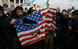 Protesters burn a US flag during a demonstration against the killing of Iranian general Qassem Soleimani in Tehran, Iran, January 3, 2020. (AP Photo/Vahid Salemi)