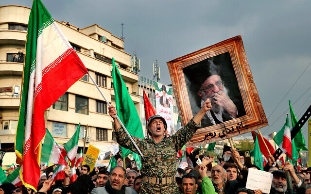 llustrative: demonstrators chant slogans while holding up an Iranian national flag during a pro-government rally in Tehran, Iran, November 25, 2019. (AP/Ebrahim Noroozi, File)