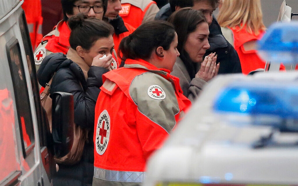 People are evacuated from the French satirical newspaper Charlie Hebdo's office, in Paris, January 7, 2015. (AP Photo/Francois Mori)