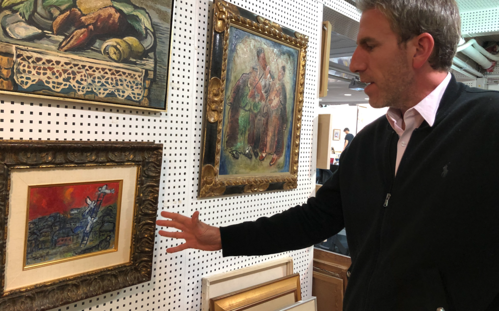Amitai Hazan Tiroche with the long-missing Marc Chagall painting, 'Jacob's Ladder,' which will be auctioned on January 25, 2020 at the Tiroche Auction House (Jessica Steinberg/Times of Israel)