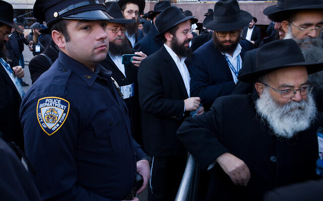 Illustrative: A New York City police officer watches as rabbis gather for a group photo at the Chabad-Lubavitch World Headquarters, in New York, November 4, 2018. (AP/Mark Lennihan)