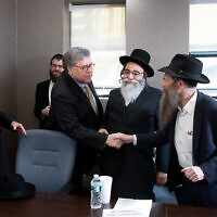 US Attorney General William Barr, center, shakes hands with Rabbi Eli Cohen, right, at a meeting with Jewish leaders at the Boro Park Jewish Community Council, Jan. 28, 2020 in New York. (AP/Mark Lennihan)