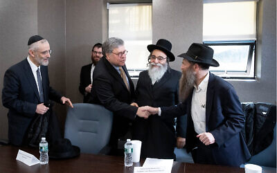 Rabbi David Niederman stands between US Attorney General William Barr and Rabbi Eli Cohen, who shake hands at a meeting with Jewish leaders at the Boro Park Jewish Community Council, January 28, 2020 in New York. (AP/Mark Lennihan)