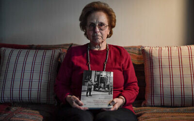 Greek Holocaust survivor Nina Camhi, 80, holds a book on the 'Holocaust of the Greek Jews' featuring her grandfather's bookstore in Thessaloniki, at her home in Athens, January 20, 2020. (Louisa Gouliamaki/AFP)