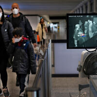 Health surveillance officers use a temperature scanner to monitor passengers arriving at Hong Kong International Airport in Hong Kong, Jan. 25, 2020. (AP/Vincent Yu)