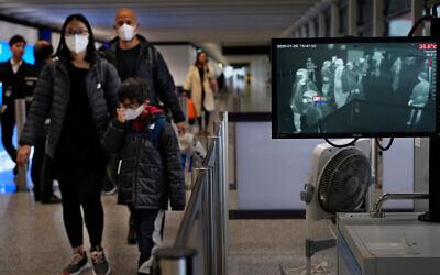 Health surveillance officers use a temperature scanner to monitor passengers arriving at Hong Kong International Airport in Hong Kong, Jan. 25, 2020. (AP/Vincent Yu)