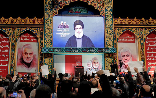 Supporters of Shiite Hezbollah terror group watch a speech by its leader Hasan Nasrallah, broadcast on a screen, in the Lebanese capital Beirut's southern suburbs, January 5, 2020. (Anwar Amro/AFP)