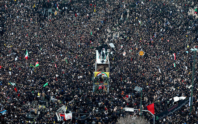 Coffins of Gen. Qassem Soleimani and others who were killed in Iraq by a US drone strike are carried on a truck surrounded by mourners during a funeral procession in the city of Mashhad, Iran, January 5, 2020. (Mohammad Hossein Thaghi/Tasnim News Agency via AP)
