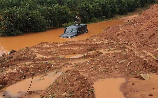 A soldier stands on the roof of his jeep after the vehicle got stuck in a deep puddle caused by recent rains in the central israeli town of Kfar Yona on January 20, 2020. (Israel Police)