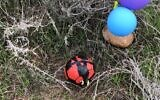 An explosives-laden soccer ball that was apparently flown from the Gaza Strip using balloons is seen in an open area of the Sha'ar Hanegev Regional Council on January 23, 2019. (Courtesy)